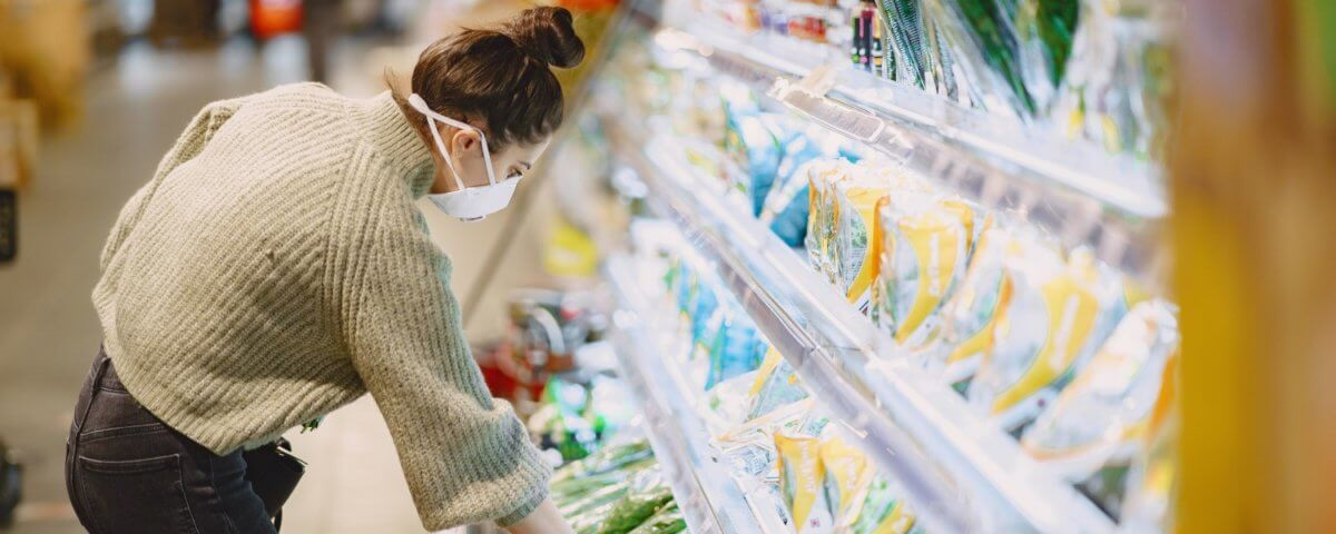 Woman with a mask shopping in a grocery store